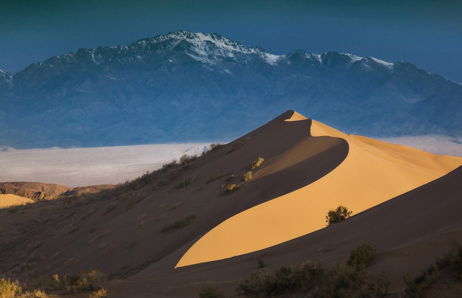 Поющий Бархан, на фоне заснеженных гор.