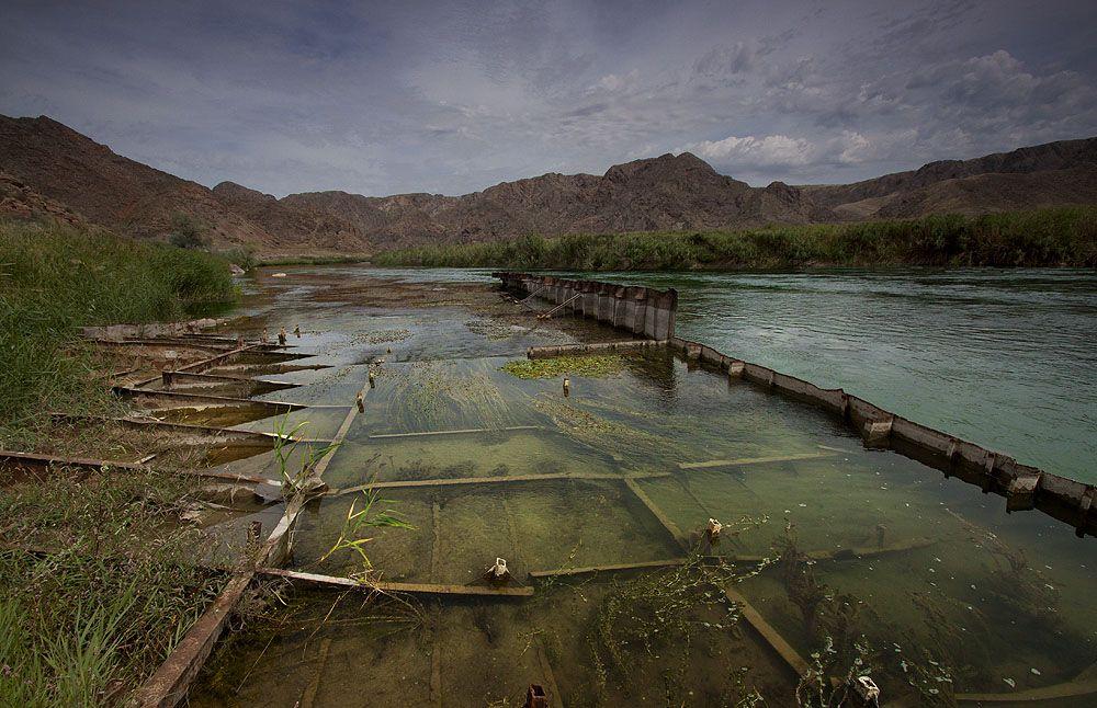 До 1959 года единственной переправой через полноводную реку Или была понтонная переправа. Весной 59 года уровень воды в реке настолько поднялся, что одна секция моста оторвалась и поплыла вниз по течению, надо сказать, что в те годы река Или была судоходная и сорвавшийся понтон мог натворить много беды. Но к счастью в 20 км вниз по течению был безымянный остров, между которым и берегом понтон застрял. Много десятилетий этот огромный ржавый монстр служил своеобразным мостиком для тех кто хотел перебраться на остров, с него было очень удобно ловить рыбу на удочку. Но пришли лихие 90е...открылись границы, за которыми сидели ловкачи и скупали за дарма ресурсы бывшего СССР...таким образом на берегу появилась техника и старый понтон который за столько времени стал достопримечательностью, просто порезали на металлолом, вот и всё что осталось от старого исполина.