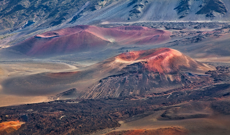 Гигантские щитовые вулканы Гавайских островов — крупнейшие в мире. Во время извержения, на поверхность земли выбрасывается вулканический туф  — осадочная горная порода, из вулканического пепла, вулканических бомб и других обломков, который может быть фиолетового цвета, известен туф красный, розовый туф, коричневого, желтого, оранжевого, реже серого и черного цвета.