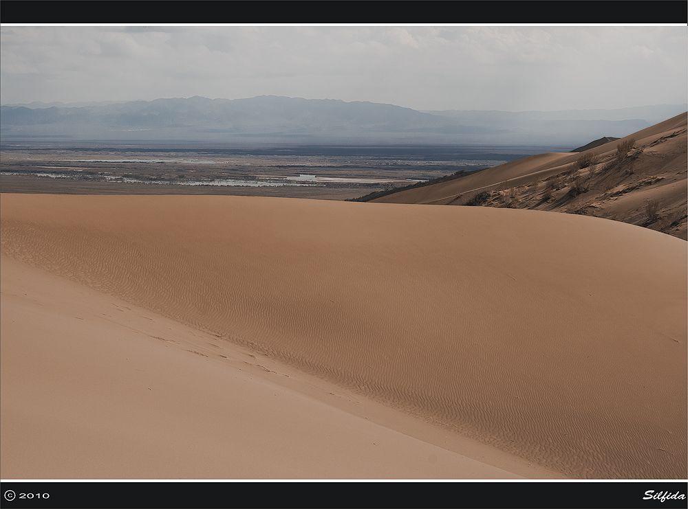 Поющий бархан, возникающий, из полупустынной степи, поражающий своим величием и сохраняющим на протяжении столетий свой неизменный вид