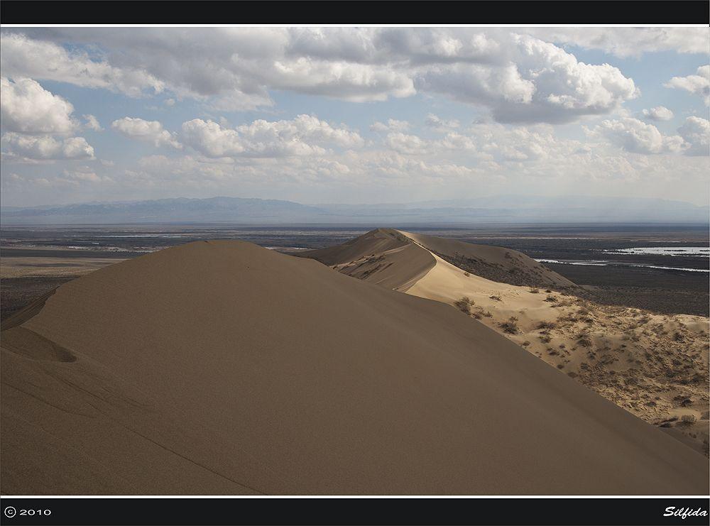 Бархан образовался в результате выдувания песков с отмелей реки Или. В данной части долины реки Или (между Калканами и горами Богуты и Сюгаты) дует сильный ветер, который поднимает с речных отмелей тучи песчаной пыли. У Большого и Малого Калканов, стоящих под небольшим углом друг к другу, ветер встречает препятствие и, ослабев, оставляет песок. Так, за многие тысячелетия, выросла громадная песчаная гора. Бархан не кочует по равнине, несмотря на зыбкость песка и сильные ветры, а остаётся на месте вот уже несколько тысячелетий.