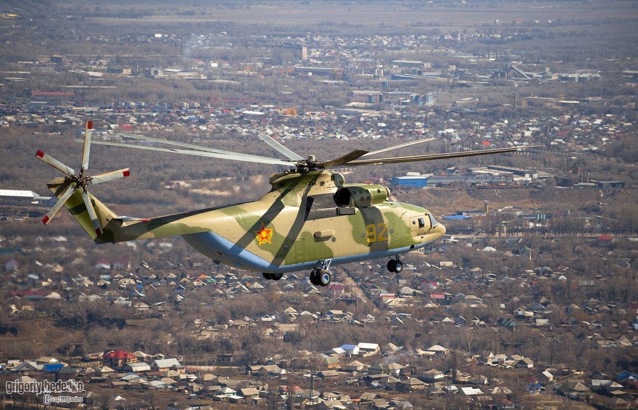 """Cегодня гигантский вертолет, кроме России эксплуатируют еще 12 стран мира, причем и в гражданском и в военном секторе. Всего было построено 310 машин, из них на момент развала Советского Союза в Казахстане оставалось 24 вертолета. Однако в 90-е годы они выработали свой ресурс и встали на прикол. Стоимость одной машины оценивается в 25 миллионов долларов, и частичное восстановление казахстанского авиапарка стало возможно лишь сейчас, когда выполняется специальная программа по технической модернизации армии. Первый модернизированный """"Ми-26"""" с бортовым номером """"91"""" поступил на вооружение 3 года назад. Экипаж этого """"Ми-26"""" состоит из 5-ти человек, а когда необходимо обслуживать специальное водосливное устройство для тушения пожаров, на борт поднимается еще один специалист – бортовой оператор. Вертолет может поднять сразу 15 тонн воды. Скорость """"Ми-26"""" 295 километров в час, а дальность полета с тремя дополнительными баками почти две тысячи километров. Таким образом, машина может взять на борт 82 десантника с полным вооружением и перебросить их с одного конца Казахстана на другой. Это незаменимая транспортная система, когда речь идет о бескрайних казахстанских степях. Также для """"Ми-26"""" достижима любая площадка в горной местности, куда невозможно добраться наземным транспортом."""