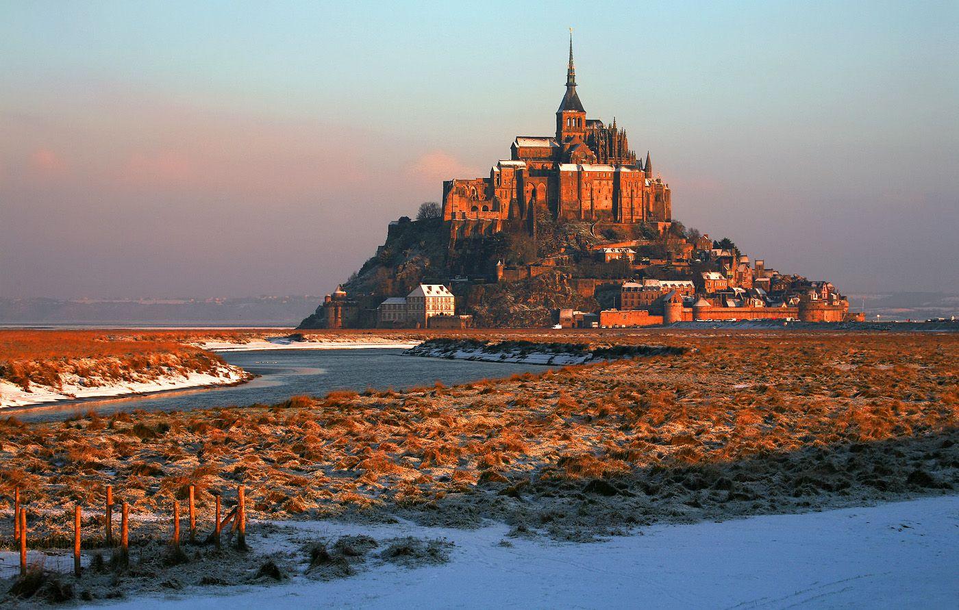 Мон-Сен-Мишель представляет собой скалистый остров, расположенный на границе Бретани и Нормандии в 400 км к северо-западу от Парижа. Это гранитная скала примерно 930 м в диаметре и высотой 92 м над уровнем моря. На ее вершине располагается монастырь и собор, посвященный архангелу Михаилу. Аббатство действует до сих пор, в нем постоянно проживает около 50 монахов-бенедиктинцев.