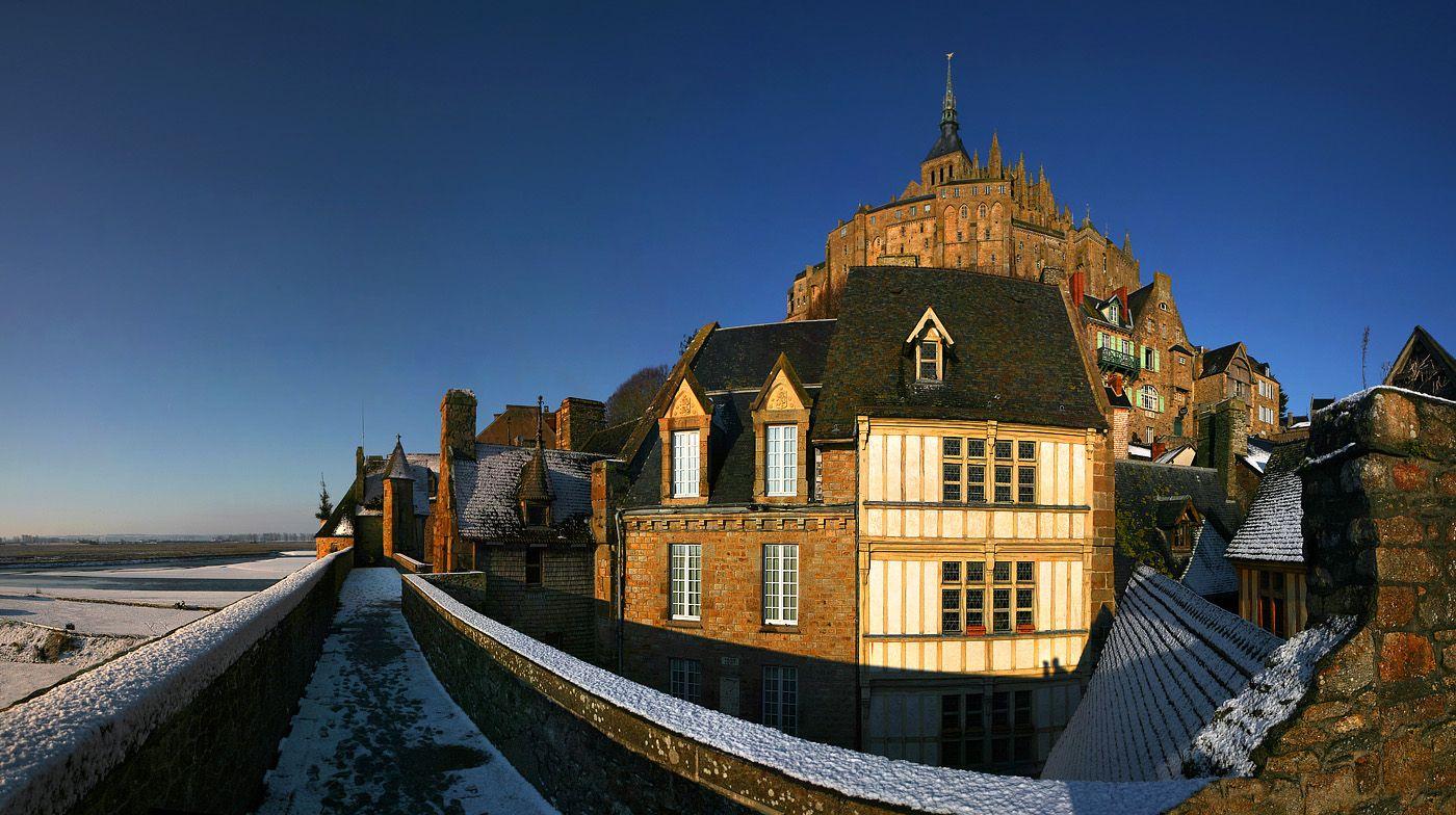 Путь в аббатство лежит через средневековый город, расположенный на южном склоне горы и окруженный крепостной стеной. Вход в город и аббатство защищает система ворот и дополнительных укреплений