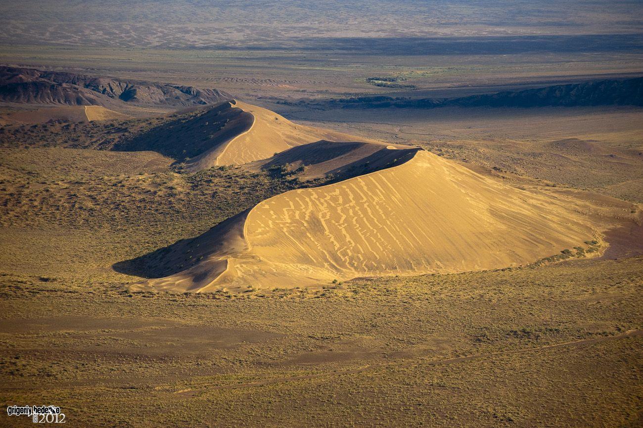 """Национальный парк """"Алтын Эмель"""". Это образование называют """"Поющий бархан"""". Место совершенно удивительное:  огромная масса песка сконцентрирована только здесь, на десятки километров вокруг ничего подобного не наблюдается. Кроме того, вокруг бархана существует какая-то аккустическая аномалия. Когда сильный ветер, или человек спускается по склону, бархан издает необычный звук, очень похожий на рев двигателя реактивного самолета."""