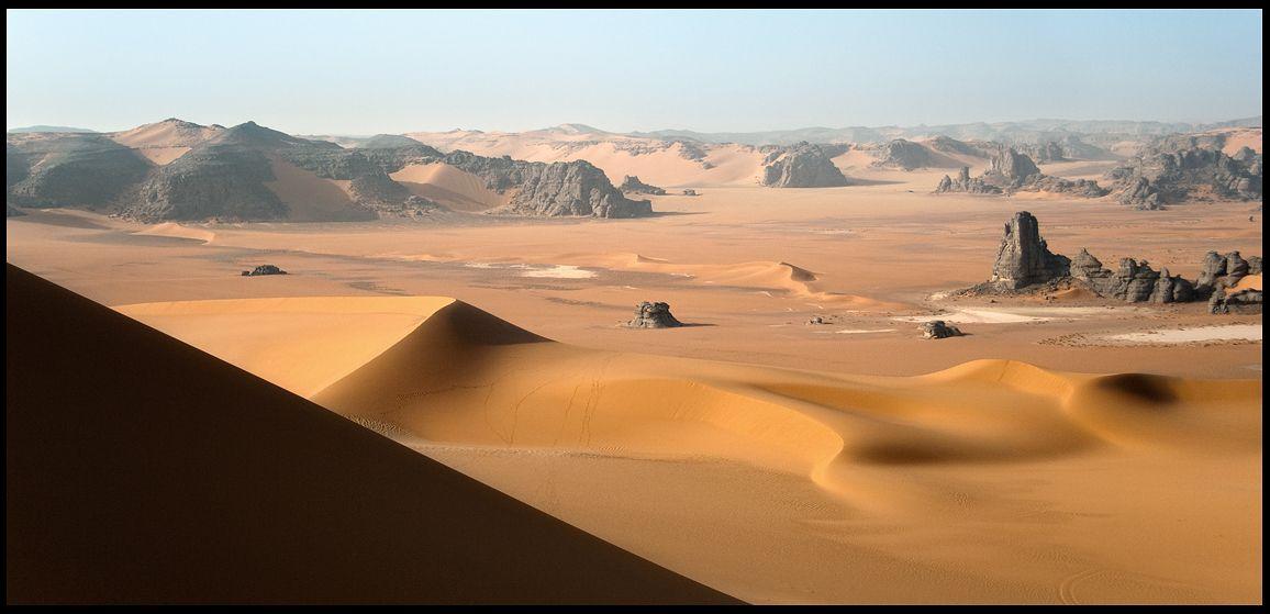 Черные скальные останцы, как корабли призраки, торчат среди желто-красного песка. Огромное пустое пространство с одной стороны и безграничность песков с другой.