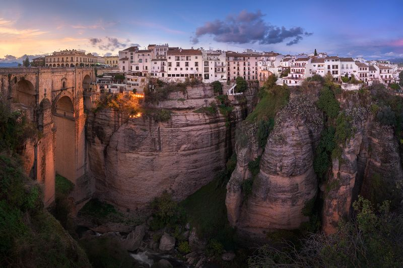 ancient, andalucia, andalusia, antique, arch, architecture, blue, bridge, building, canyon, chasm, city, cityscape, cliff, dusk, europe, european, evening, gorge, high, hill, historic, historical, history, house, iberia, iconic, illuminated, landmark, lan Panorama of Puente Nuevo Bridgephoto preview