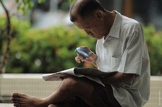 Житель Джордж тауна, читает утреннию газету.