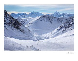 Вид с перевала. Прямо в хребте Куйлю видны (слева направо) пик Карпинского (Менсу) (5100) и пик Конституции (5281).  При переходе через перевалы в восточной части хребта Терскей Ала-тоо внимание путешественника невольно привлекают далекие грандиозные ледяные пики восточной части хребта Куйлю. Освоение района альпинистами началось в 1936 году разведочной экспедицией А. А. Летавета. Вершину назвали тогда пик Сталинской Конституции. Позже, в 70-80х годах прошлого века вершину называли пик Советской Конституции, а уже сегодня ее называют просто – пик Конституции. Тогда же было совершено восхождение на соседнюю вершину, получившую название пик Карпинского.  Путешественники прошлого столетия, наблюдавшие хребет Куйлю с верховьев р. Сарыджаса, высказали предположение, что главная вершина Куйлю лишь немного уступает по своей высоте Хан-Тенгри. В 1900 году Центральный Тянь-Шань посещает доктор Георг фон-Алмаши из Австро-Венгрии. Высшую точку хребта Куйлю Алмаши называет пиком Эдуарда (в честь своего отца Эди – одного из основателей Венгерского Географического общества). Сейчас эта вершина ивестна как пик Конституции. В 1902 году проф. В. В. Сапожников перешел через перемычку, соединяющую хребты Куйлю и Терскей (перевал Куйлю) и обогнув хребет Куйлю с запада, спустился в ущелье р. Теректы. Однако достичь юго-восточного угла хребта, где расположены главные вершины Куйлю, ему не удалось.  «Летом 1936 г. самодеятельная группа автора этих строк поставила себе задачу несколько раз пересечь Куйлю в его восточной части и определить характер и местоположение основных вершин. Задача эта была выполнена. Были пройдены ущелья Б. и М. Талды-Cу и найдены перевалы в систему р. Теректы. ...В начале августа 1936 г. группа альпинистов после утомительного дневного перехода уже к вечеру поднялась на седловину, замыкающую ледник Б. Талды-Cу. На седловине вся группа остановилась, как очарованная. В лучах вечернего солнца сверкала перед альпинистами прекрасная, стройная вершина, скованная льдами. О