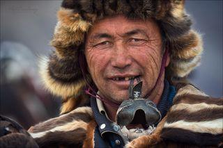 В зубах охотник держит кожаный клобучок ( называется «томагу» ), который одевают на голову беркута и тем самым закрывают ему глаза. Основное его предназначение - он защищает птицу от ненужных внешних зрительных раздражений)