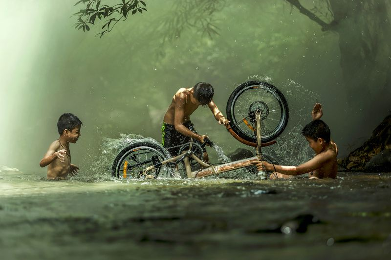 #summer. #Bicycle #Candid #Child #Children Only #Color Image #Day #Horizontal #Outdoors #People #Photography #Pre-Adolescent Child #Real People #Sunlight #Thai culture #Three Boys #Togetherness #Tradition #Transportation #Two People #Wading #Washing #Wate The boys are washing bicycle playfully River Near Homephoto preview