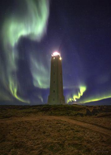 Northern lights dance around lighthouse.